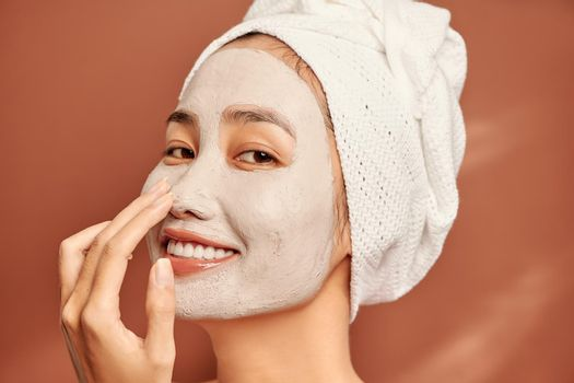 Beautiful Asian woman applying facial mask on her face. Skin care and treatment, spa, natural beauty and cosmetology concept.