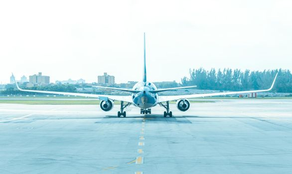 Back view of airplane standing on runway at aerodrome
