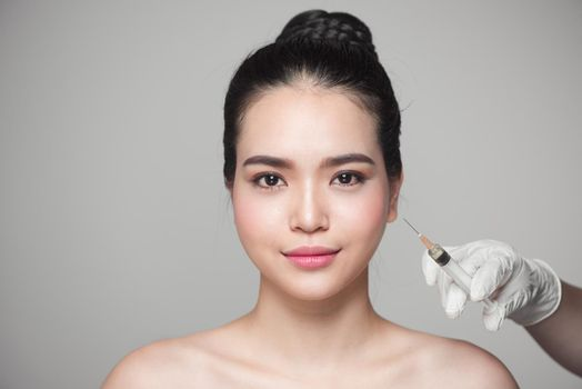 Beautiful asian woman gets beauty facial injections. Face aging injection.