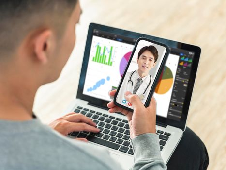 Back view of man talking by video call with his doctor.