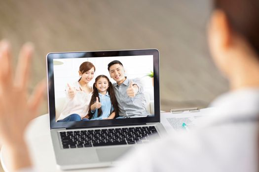 Back view of doctor talking to family by video call with laptop.
