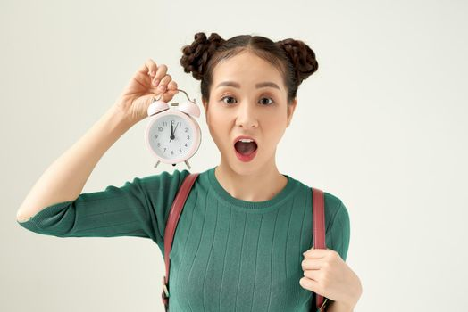 Image of screaming young confused woman standing isolated over white background. Looking aside holding alarm clock.