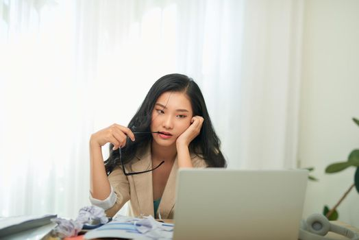 Young Asian worker woman working with laptop computer. A woman thinking of some idea and feeling stress while working from home