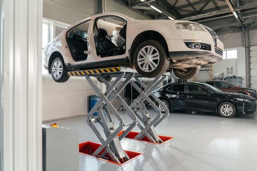 Car on hydraulic lift at auto repair shop. Auto sevice concept