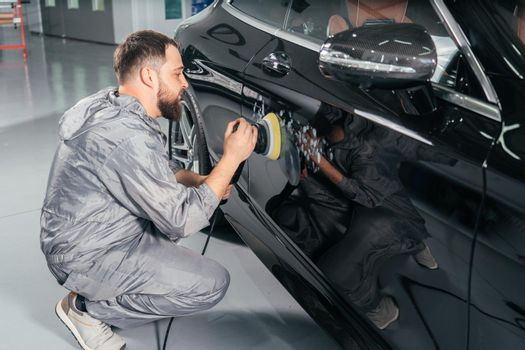 Worker polishing car with special grinder and wax from scratches at the car service station. Professional car detailing and maintenance concept