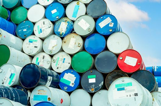 Old chemical barrels with flammable liquid warning label . Steel oil tank. Toxic waste in metal tank. Hazardous chemical barrel. Hazard waste storage in factory. Chemical barrels stack. Oil brent.