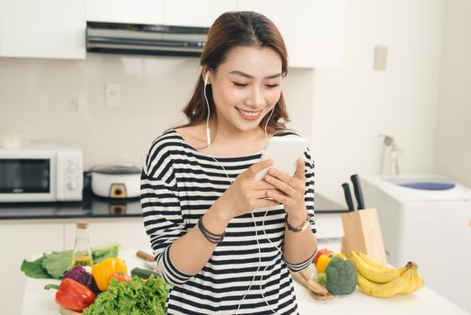 Young Vietnamese woman using smartphone at home with earphones