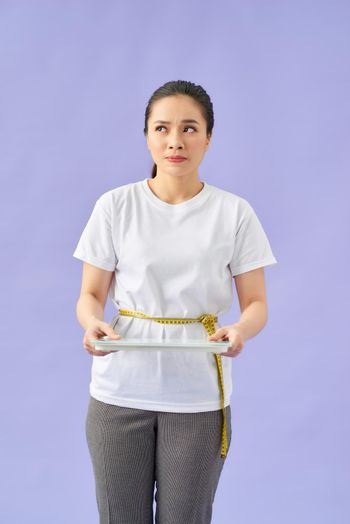 Woman with scale unhappy with her weight gesturing sadness and worry on purple