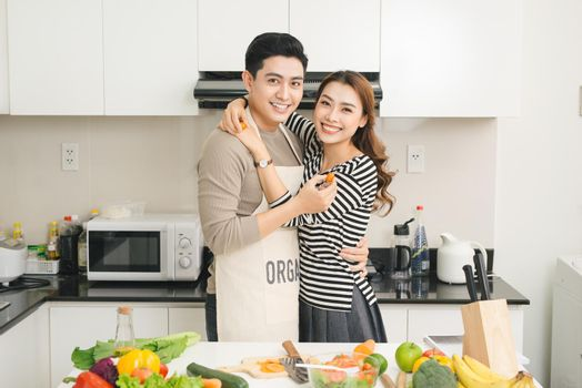 Loving Vietnamese couple cooking together in the kitchen at home