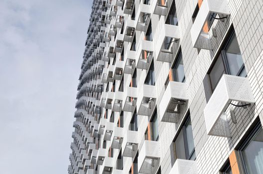 The facade of a new multi-storey residential building with windows and compartments for outdoor units of split systems.
