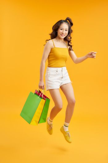 Joyful Teen Summer Girl Carrying Shopping Bags And Jumping In Air Over orange Background, Full-Length Shot With Copy Space