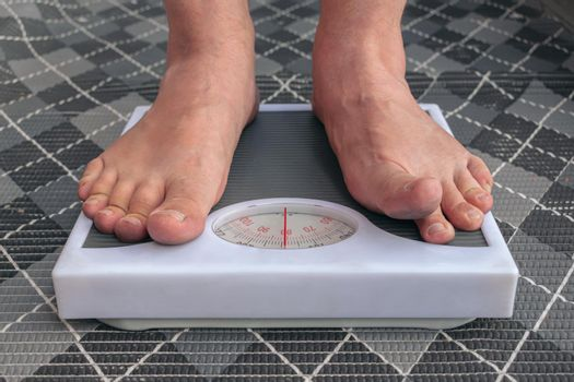 A young man is weighed barefoot on the scales in order to control his weight and follow a diet