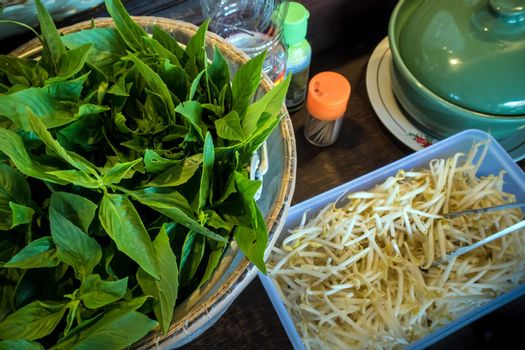 Fresh basil and bean sprouts and equipment and a flavoring for serving customers at the noodle shop