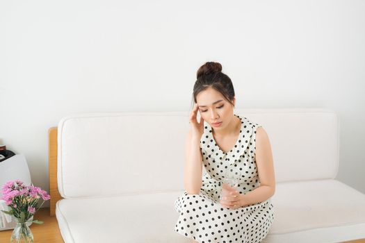 Upset Vietnamese woman on couch at home in the living room