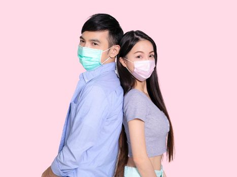 Young couple standing back to back with mask