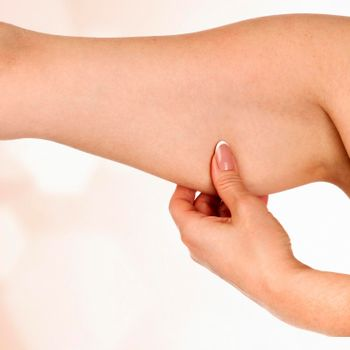 Woman holding her hand with excess fat against an abstract background with light flares and copyspace