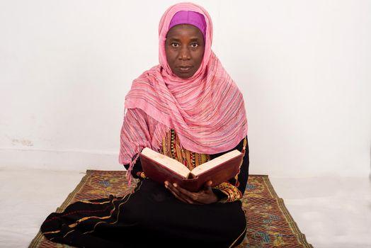 Muslim woman sitting praying reads the Koran