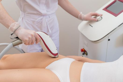 A woman in a professional beauty salon removes unwanted vegetation in the bikini area using laser hair removal