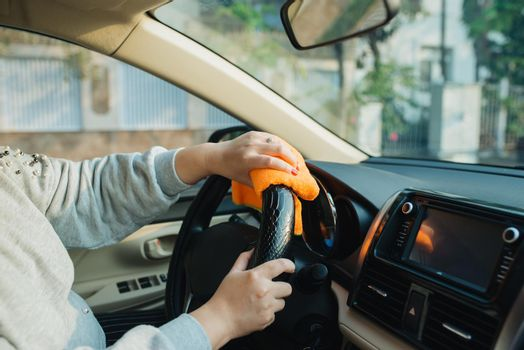 Hand with microfiber cloth cleaning seat, auto detailing and valeting concept, washing car care interior, selective focus