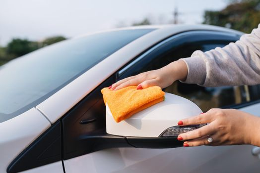 A woman cleaning car with microfiber cloth, car detailing (or valeting) concept