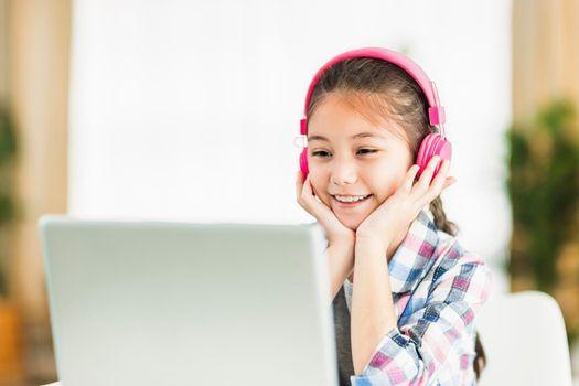 Happy student girl in headphones.Study online on laptop listening course.