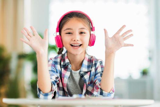 Happy student girl in headphones,saying hi,look at camera.