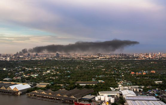 Plume of smoke clouds from Burnt industrial or office building on fire at some area in the city.
