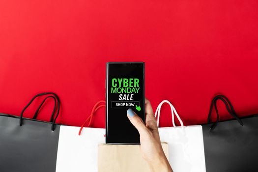 Cyber Monday Sale Clearance Discount Concept, woman hand holding smartphone with shopping bag.
