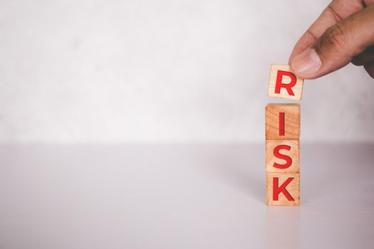 Planning with finance and investment for strategy of business, uncertainty and risk, instability for economy, hands of businessman put cube wooden block stack with word RISK, business concepts.