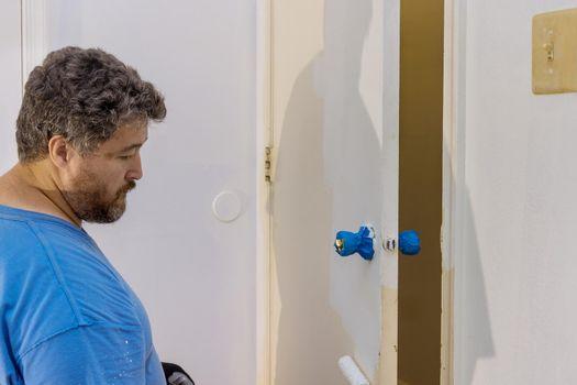 Repairman carpenter working painting a wooden door