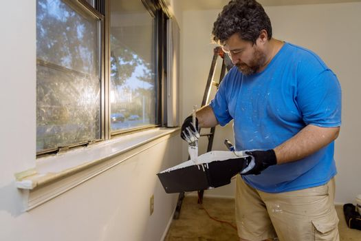Home renovation in the handyman paints with a paint brush a window molding frame