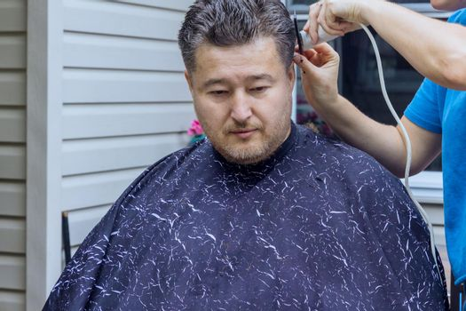 A hairdresser stylish haircut for a man in a home