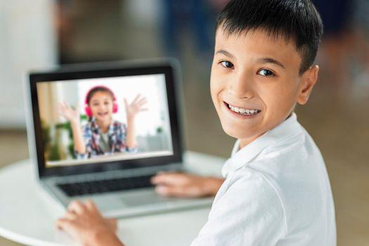 Happy boy meet his classmate online with laptop.