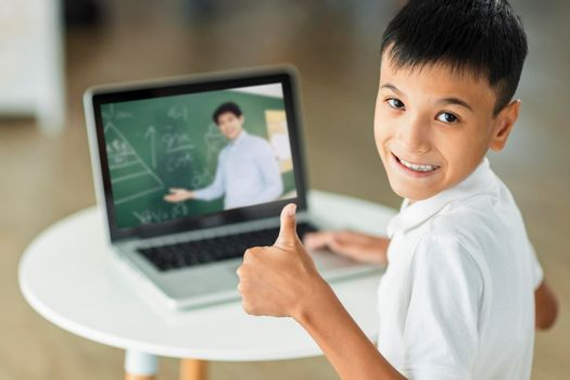 Boy study online with laptop.Looking at camera and showing thumb up.