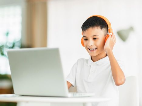 Boy wearing headphones and studying online with laptop.