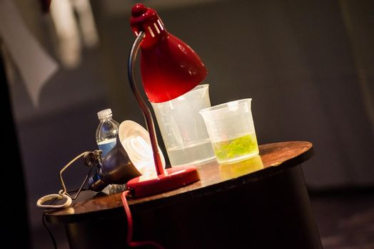 Science experiment materials including colorful green liquid filled cup.