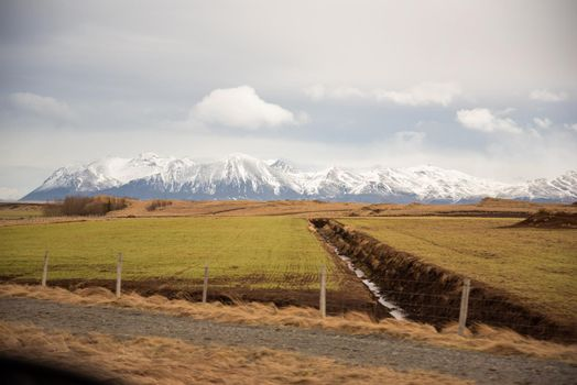 Iceland terrain of beautiful green and orange colors with waterway creating lines leading into a blue snow capped mountain range with puffy clouds dramatic heavenly farmland fencing.