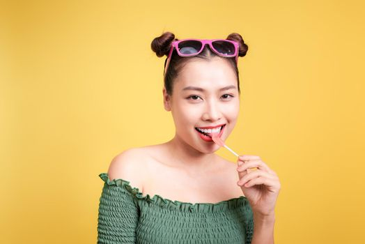 Glamor stylish beautiful young woman model with red lips holding candy on yellow background.