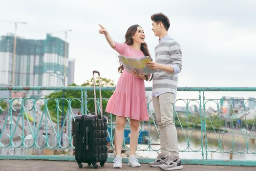 Happy asian couple on vacation sightseeing city with map