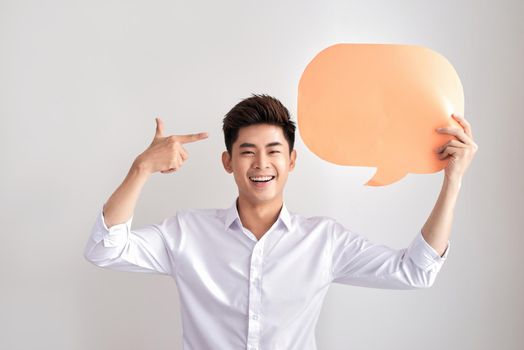 Joyful thinking man holding white empty speech balloon with space for text isolated on white background.