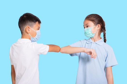 Boy and girl in medical mask bumping their elbows.Isolated on blue background.
