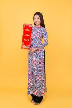 Full-length portrait of Vietnamese girl in ao-dai dress showing New Year scrolls