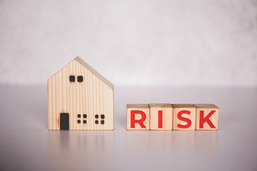 Planning with finance and investment for strategy of business about real estate with risk, uncertainty for economy, cube wooden block with word RISK and home, safety and insurance, business concepts.