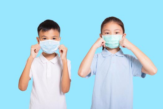 Boy and girl in medical mask. Isolated on blue background.