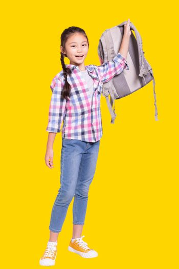 Full length portrait of a happy student girl with bag.Isolated on yellow background.