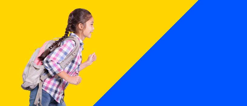 Happy student girl with school bag.Ready to run.Isolated on yellow and blue background.