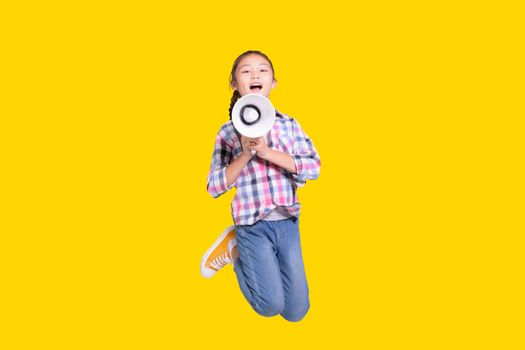 Girl jumping with megaphone.Isolated on yellow background.