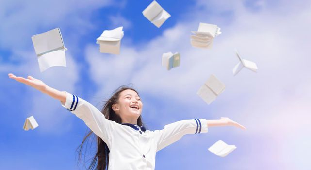 Happy school girl student throwing books fly in air
