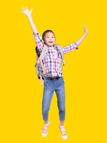 Full length portrait of a happy student girl with bag and jumping.Isolated on yellow background.