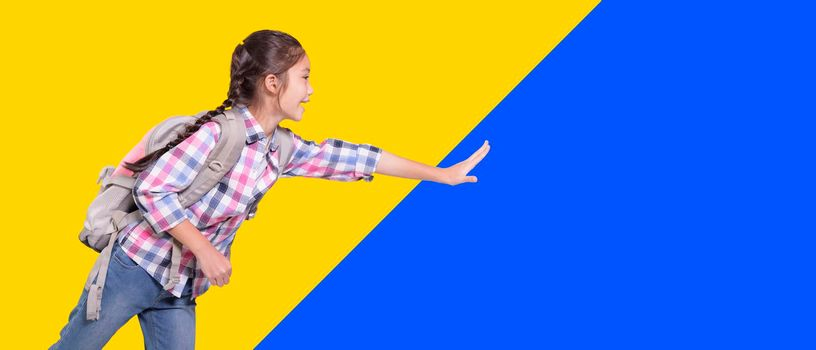 Happy student girl with school bag. Running and touching something. Isolated on yellow and blue background.